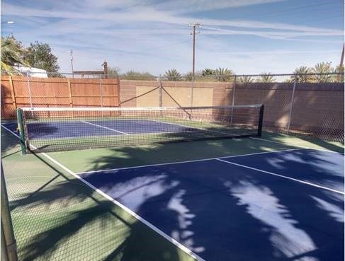 A pickleball court that looks similar to a tennis court with four blue squares and the color green on the side that is similar to the color of pickles so that may be why it's a pickleball court perhaps and there is a brown fence surround the court so no one gets hit on the face as they pass by.