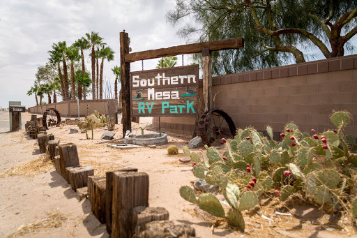 Southern Mesa RV Park on wooden plank swinging sign as big as the wall behind it with a wooden water wheel below and cactuses on the right corner and palm tree behind the sign with sand that is a light tan color.
