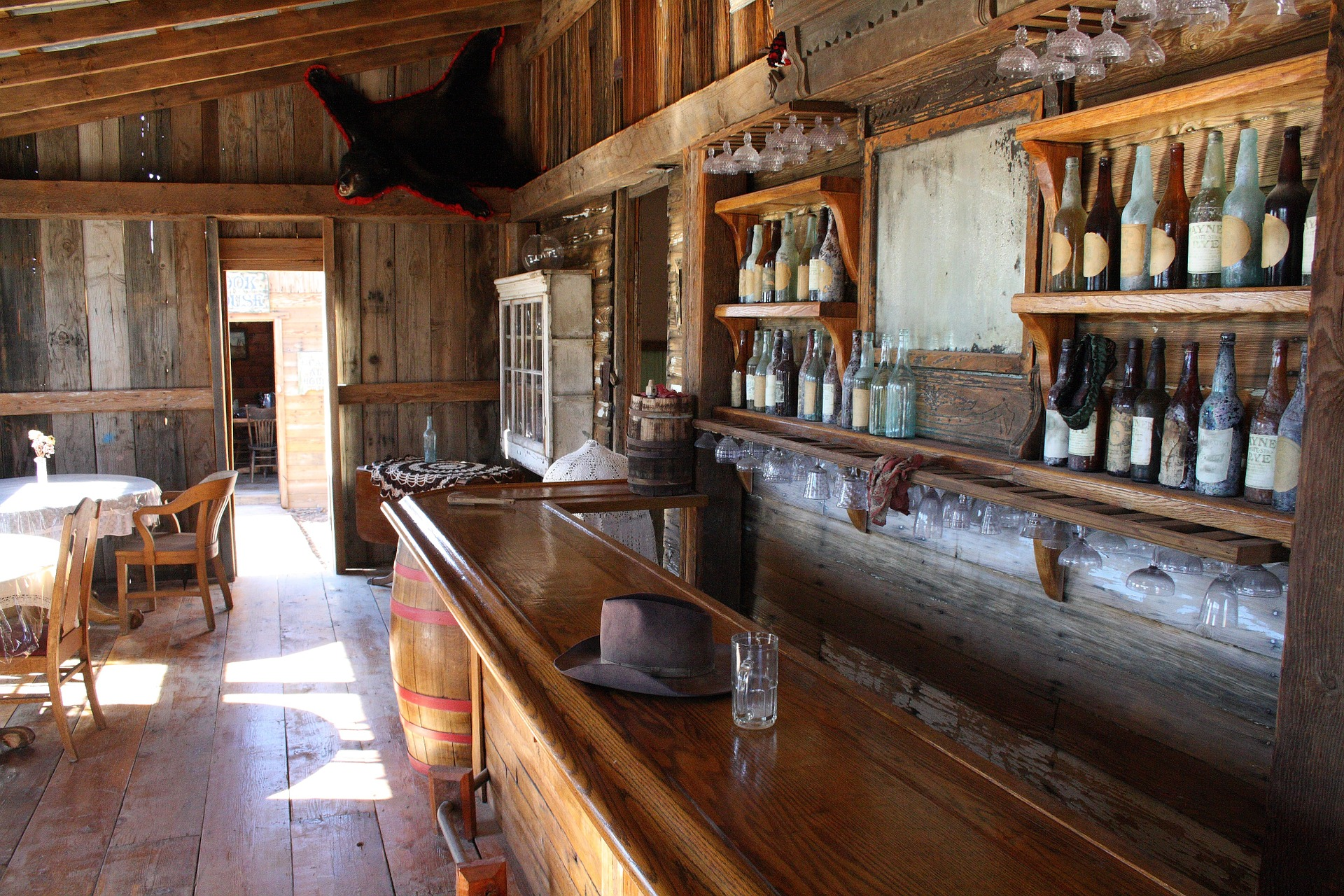 An old western bar with shine on the floor and bright inside with wood and bottles on the shelf to the right.