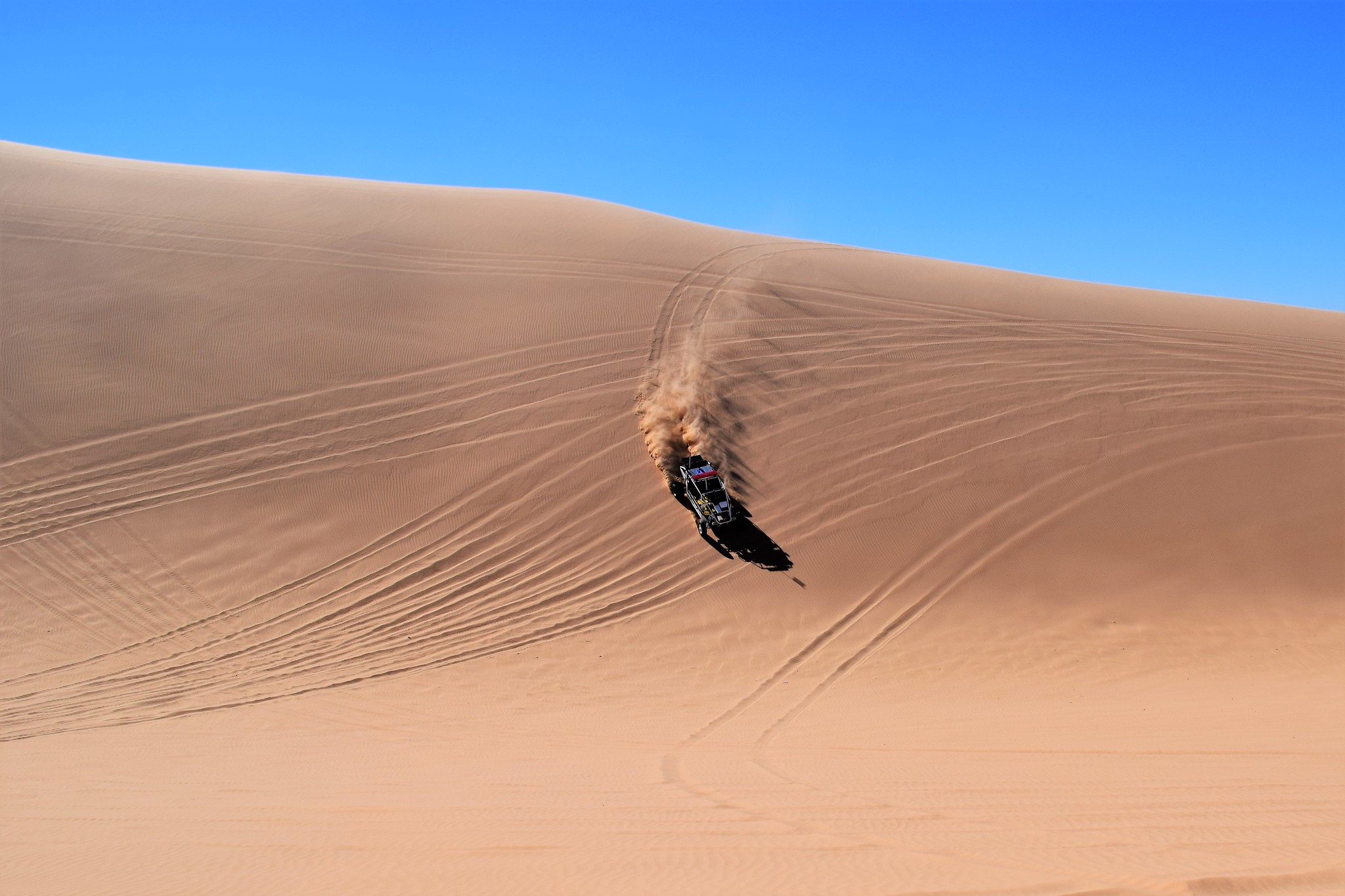A horizon photo of sand and a vehicle being driven fast on the sand with one fourth of the upper top of the photo in blue sky.