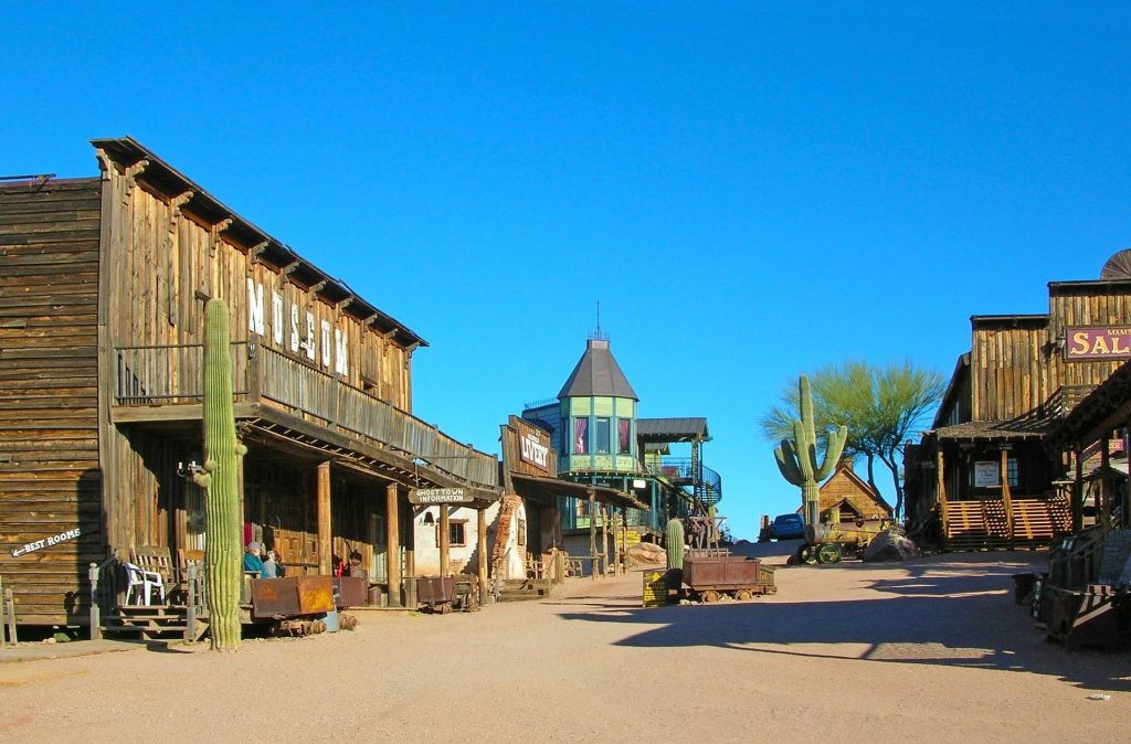 The hero image banner with a gradient of darker blue up top and light blue on bottom as the sky and in front of the sky is an old west sort of look with little towns and a building that resembles a saloon on the left and more smaller western buildings on the right.