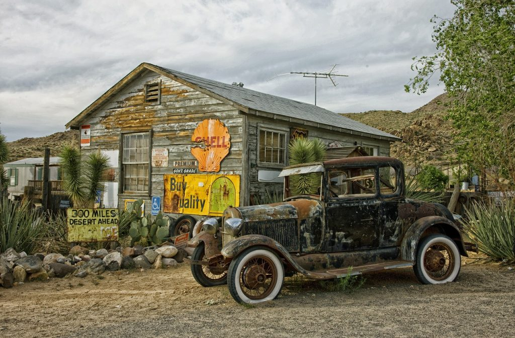"""Old vehicle in front of an old cabin with the words """"Shell"""" and """"Buy Quality"""" as signs on the dilapidated cabin."""