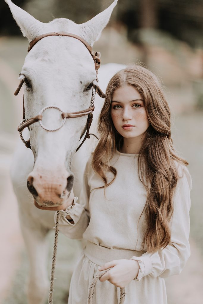 Beautiful woman with wavy chestnut brown hair dressed in a white sweater holding the rein of a white horse and posing with a serious expression like she's reading to take on the world riding her white horse and taking charge of her life like the independent woman she is!
