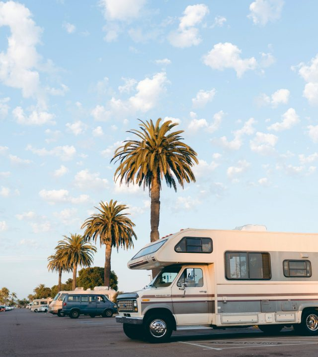 RV in parking lot with three palms trees angled down with light blue sky and white clouds.